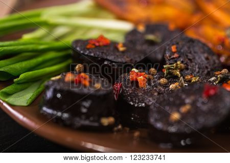 macro image of black pudding sausage with spices on a cutting board