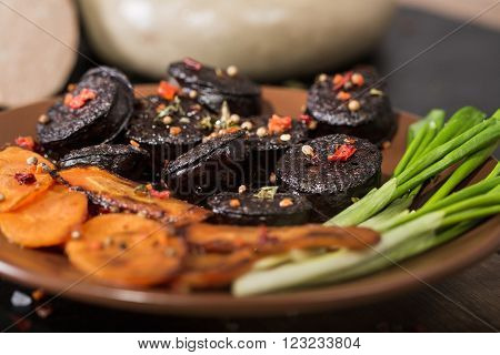 macro image of black pudding sausage with spices on a cutting board ** Note: Shallow depth of field