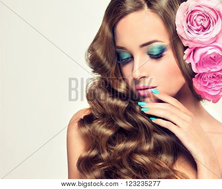 Beautiful girl with long wavy hair.  Brunette  model with curly hairstyle roses  flowers in her hair. Cosmetics, makeup and manicure nails.