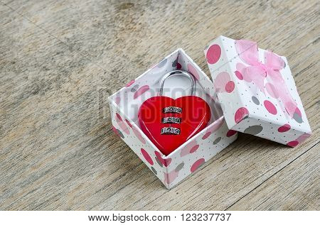 Red padlock heart shape in gift box on wooden background.