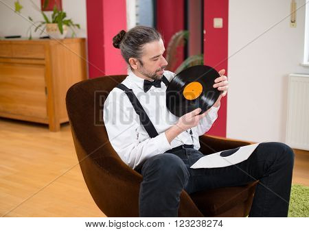 Man In White Shirt With Bow-tie With Old Records In His Living Room