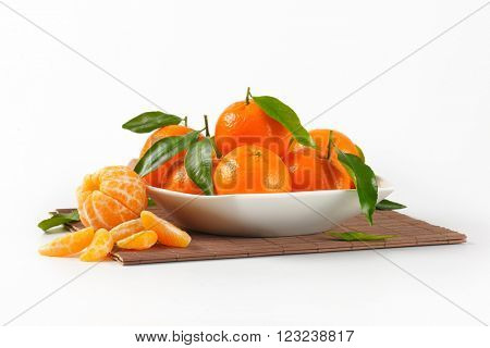 bowl of ripe tangerines on brown place mat