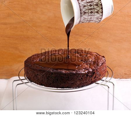 Pouring chocolate icing over chocolate sponge cake