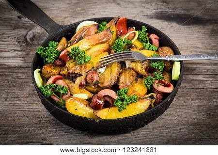Irish sliced fried potatoes with sausages in pan