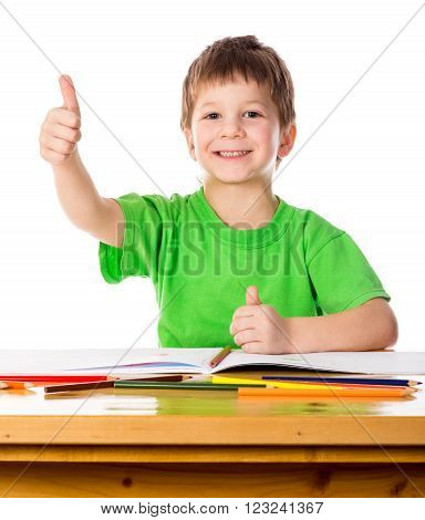 Creative little boy at the table with thumb up sign, isolated on white