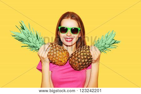 Fashion portrait pretty smiling woman and pineapple in sunglasses over yellow background