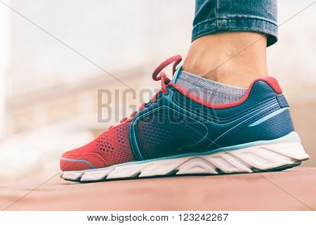 Women's foot in red and blue sneaker close-up low angle shooting