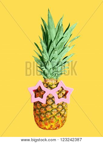 Pineapple with sunglasses on yellow background, colorful ananas