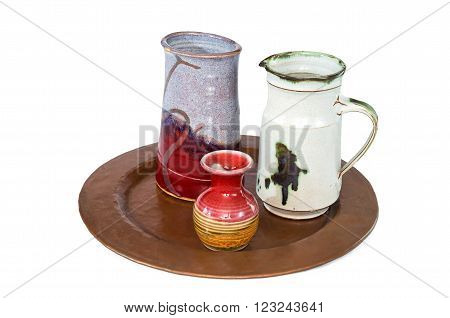 trio of small ceramic pottery includes vase pitcher and ewer on copper serving tray isolated against white
