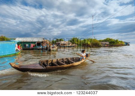 SIEM REAP, CAMBODIA DEC. 16: Cambodian people live on Tonle Sap Lake in Siem Reap, Cambodia on December 16, 2011. Children swim to school by boat.