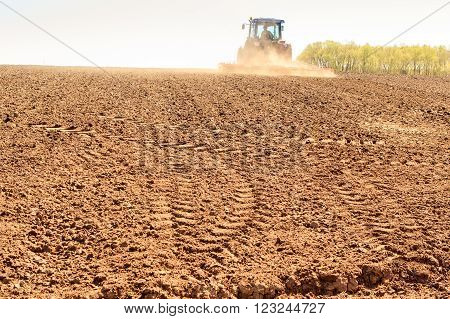 distant tractor cultivator leaves fresh track on wet brown ploughed field against far forest