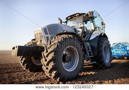 Closeup Side View Seeder On Big Wheels On Ploughed Field