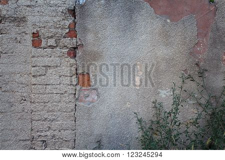 Cracked and obsolete grey plastered brick wall