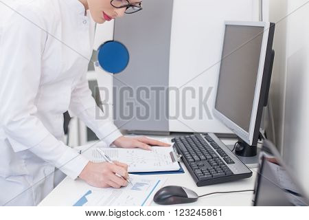 Professional young scientist is writing down her findings. She is standing near the table and looking at the documents with concentration