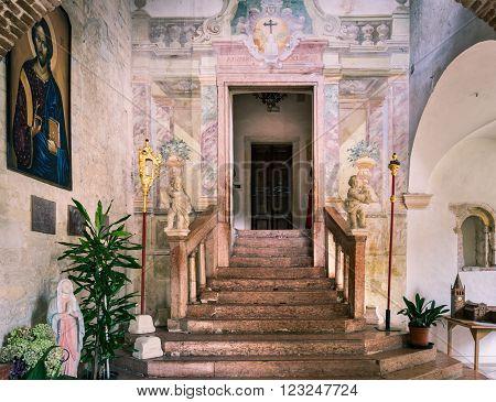 Villanova Italy - September 07 2015: Door leading inside the Romanesque church from exterior cloisters.