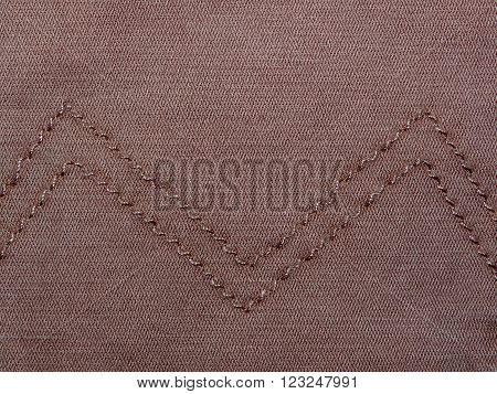 plain brown fabric with a stitched seam of thread made of cotton, has a small crease