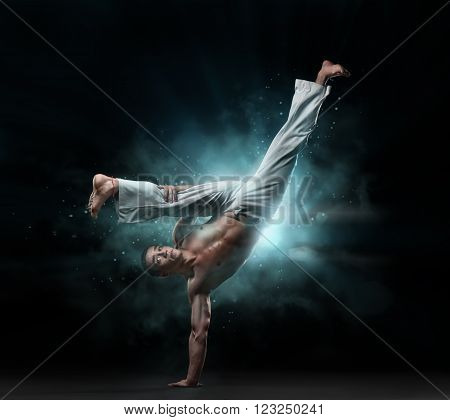 male fighter trains capoeira on a black background in the light