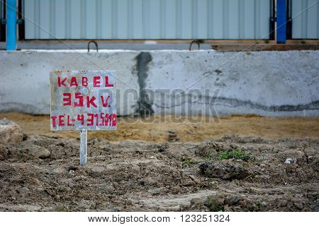 BAKU - AZERBAIJAN - JANUARY 16 2015 35kV warning sign in construction sign in Baku, capital of Azerbaijan. A hand painted sign on a building site, advising of high voltage cable