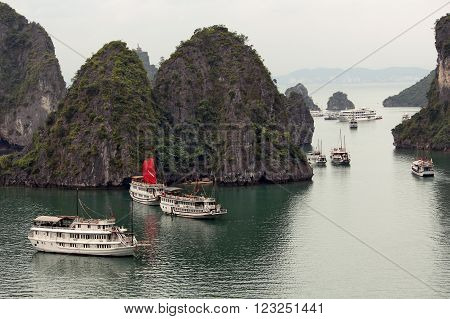HALONG BAY, VIETNAM. 05 APRIL  2015.  Tourist Cruise boats with red sails floats in the bay according to the standard sightseeing program.