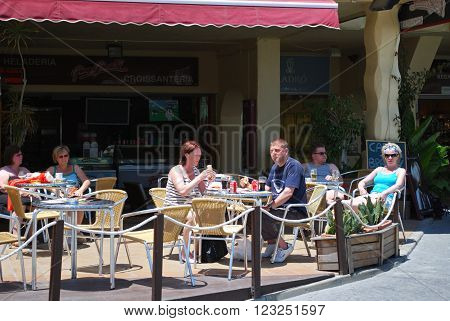 BENALMADENA, SPAIN - JUNE 2, 2008 - Tourists relaxing at a pavement cafe in the port area Benalmadena Costa del Sol Malaga Province Andalusia Spain Western Europe, June 2, 2008.
