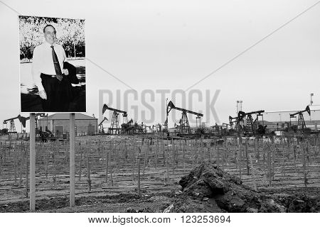 BAKU, AZERBAIJAN - JANUARY 27 2014  Photo of Heydar Aliyev in front of Baku oil field, Azerbaijan. An on-shore oil field with picture of the former president of Azerbaijan