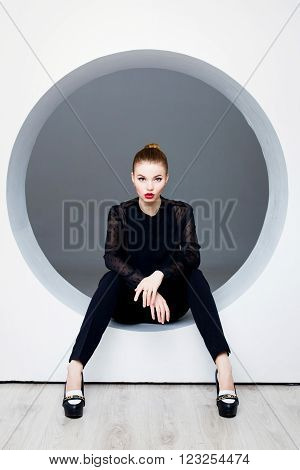 Sexy woman posing in circle hole in wall