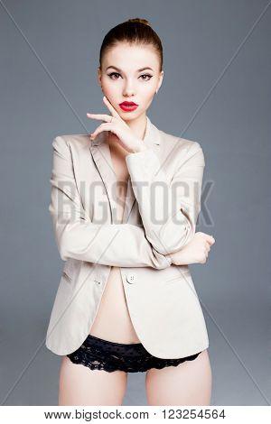 Sexy seductive brunette female fashion model in jaket posing in studio