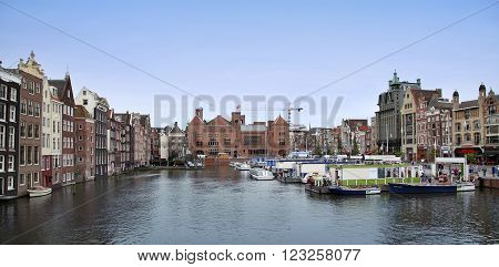 AMSTERDAM; THE NETHERLANDS - AUGUST 16; 2015: Beautiful views of the ancient buildings at the waterside, canal and boats, Damrak canal in Amsterdam, The Netherlands on August 16; 2015.