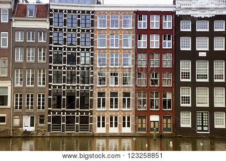 AMSTERDAM; THE NETHERLANDS - AUGUST 16; 2015: Beautiful views of the ancient buildings at the waterside, Damrak canal in Amsterdam. Amsterdam is capital of the Netherlands on August 16; 2015.