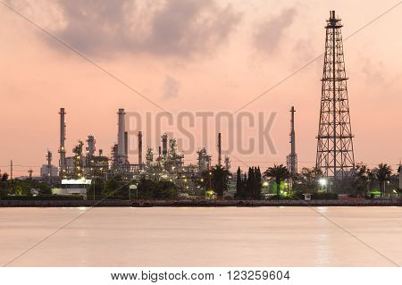 Oil manufacturing plant riverfront during sunrise, heavy industrial