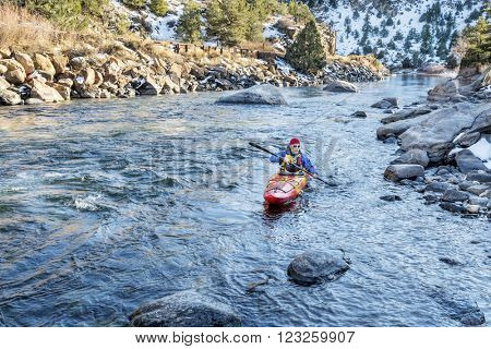 senior kayaker in a whitewater kayak paddling upstream of Arkansas River above Hecla Junction, Colorado in winter scenery