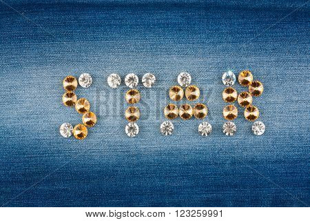 Inscription STAR made of rhinestones on jeans background