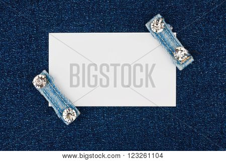Business card with two straps jeans with rhinestones lies on the denim with space for your text