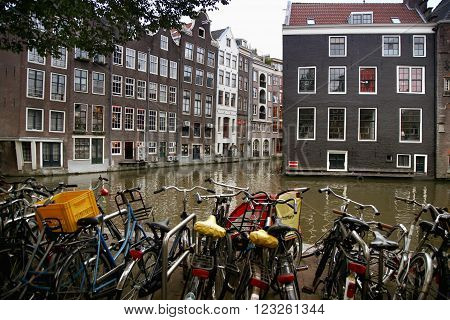AMSTERDAM, THE NETHERLANDS - AUGUST 18, 2015: View on Oudezijds Kolk canal, street life, bicycle, canal in Amsterdam. Amsterdam is capital of the Netherlands on August 18, 2015.