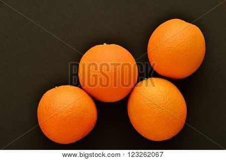 orange.oranges.four oranges.Four goals oranges.oranges on a black background.