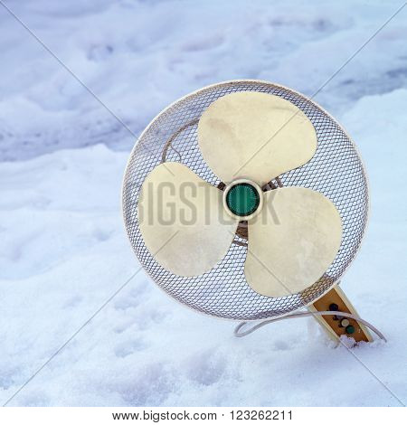Abandoned floor fan stuck in the snow concept of weather and climate change