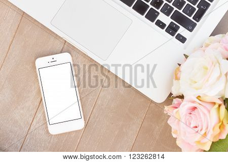 styled gray wooden desktop with modern phone, pc keyboard and flowers