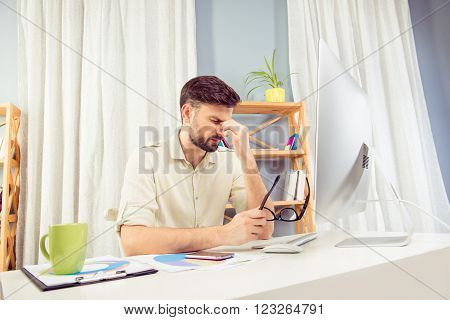 Depressive Tired Young Man Sitting In Office And Thinking