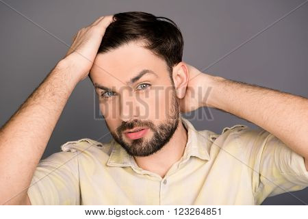 Handsome Cheerful Young Man Combing His Hair With Fingers