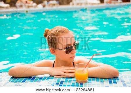 Sexy girl in a pool with juice and glasses