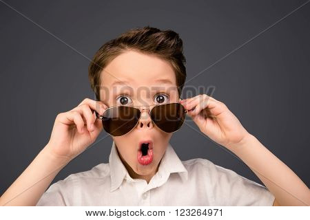 Portrait Of Little Surprised Kid In Glasses With Open Mouth