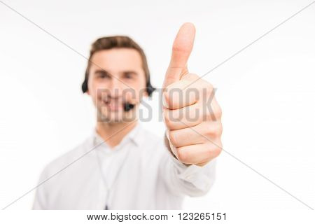 Smiling young agent of call centre showing thumb up, focus on hand