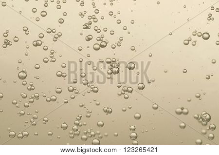 Many small golden fizz bubbles in a crystal glass