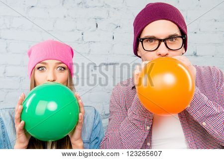 Close Up Photo Of Two Lovers Inflating Balloons For Celebration
