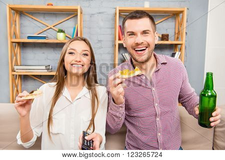 Portrait Of Happy Man And Woman Watching Comedy And Eating Pizza