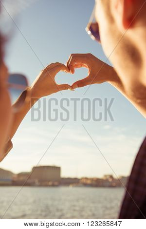 Couple In Love Gesturing A Heart With Fingers On A Background Of Sky