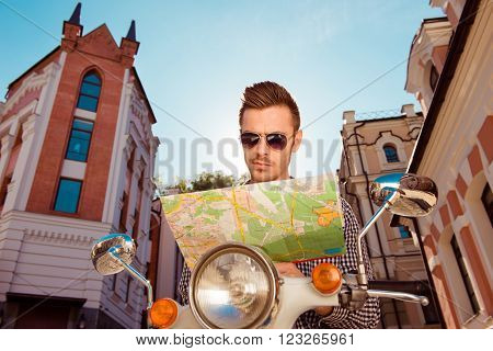 Young Man With Glasses Sitting On The Motorbike Looking At The Map