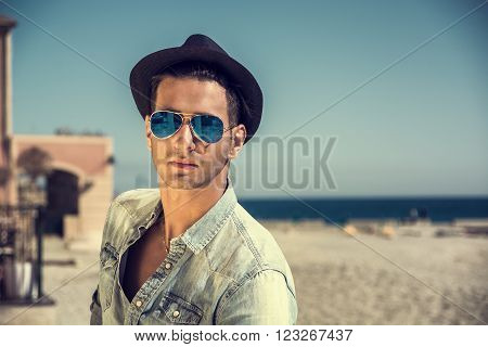 Three Quarter Shot of a Handsome Athletic Young Man in Trendy Attire, on a Beach in a Sunny Summer Day, Looking At Camera wearing sunglasses and hat, against Blue Sky Background.