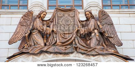 Ancient sculpture depicts two archangels with a book in their hands