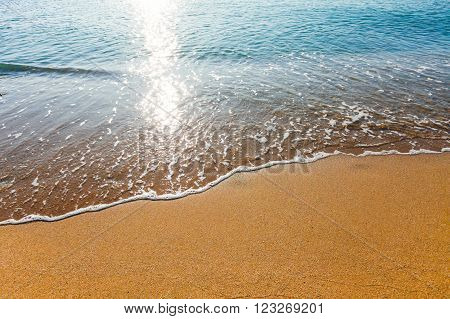 Soft wave of the sea washing foot marks from the sandy beach